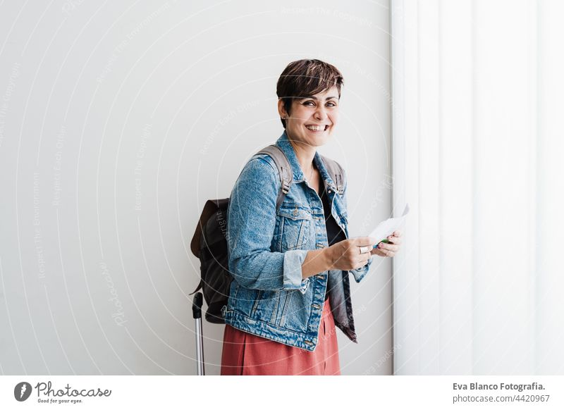 happy backpacker caucasian woman at train station holding ticket waiting to catch train. Travel concept travel public transport young suitcase luggage baggage