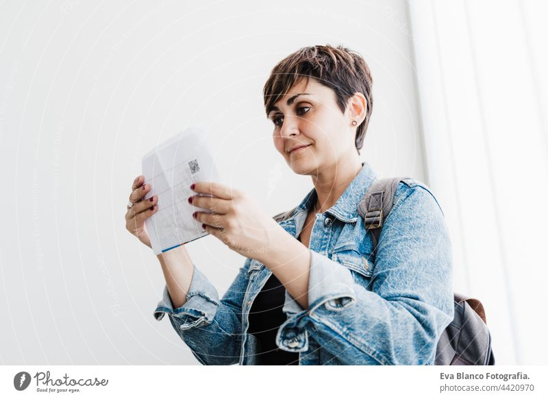 beautiful backpacker caucasian woman at train station holding ticket waiting to catch train. Travel concept travel public transport young suitcase luggage
