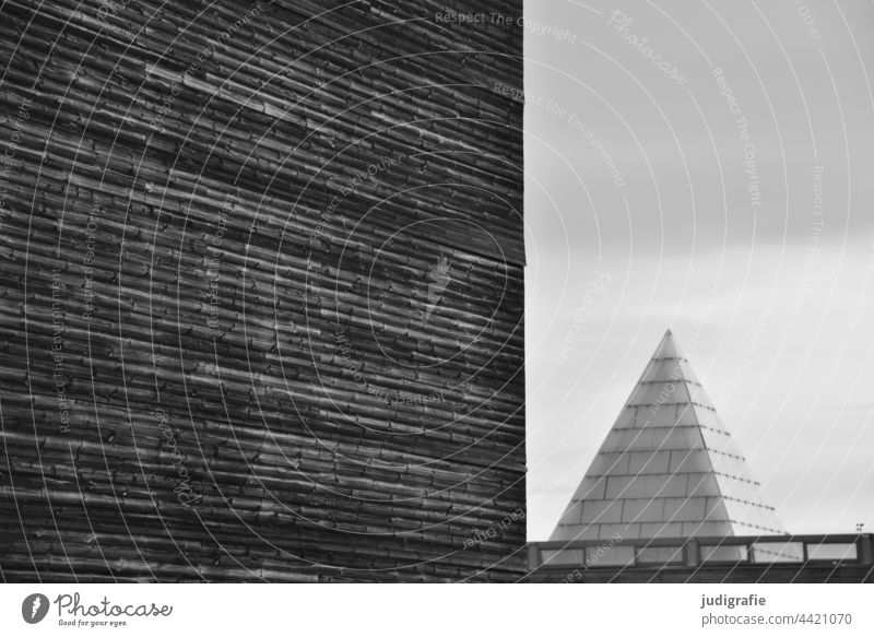Structured facade next to glass pyramid Architecture Facade Pyramid Glass Modern Point Triangle surface Building Manmade structures lines geometric Design
