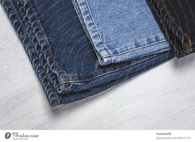 Handicraft, clothing repair. Ripped blue jeans sewing accessories tailor fix patch background White custom pocket denim tools crafts hem recycling garments
