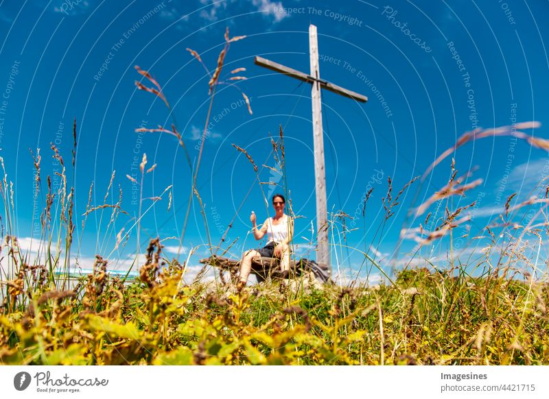 Blurred. Summit cross at the top of the mountain in the Bavarian Alps with a climber giving the thumbs up. Arrived, victory pose at the top of a mountain cross. Focus on grass.