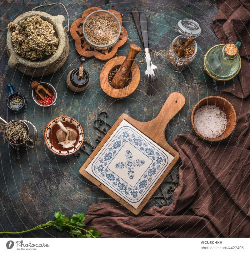 Various rustic aged kitchen utensils on dark table background with chopping board, forks and dried condiments. Top view various top view cooking cuisine food
