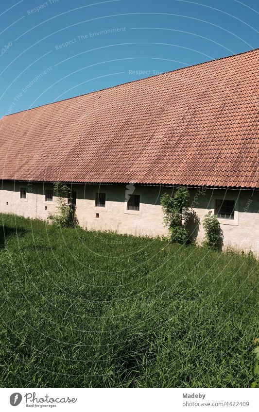Big stables of an old farmstead in front of a blue sky in sunshine at Brake Castle in Lemgo near Detmold in East Westphalia-Lippe Barn Farm Estate Building Roof