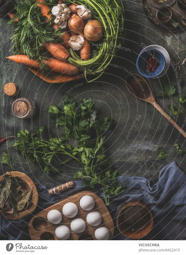 Healthy ingredients for tasty cooking at home. Fresh vegetables and herbs on a dark kitchen table with a wooden spoon, fresh eggs and dried seasonings . Top view