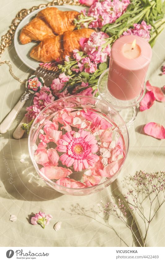 Glass water bowl with pink flowers on picnic blanket with Croissants and candles. Sunny day. Aesthetic picnic concept glass croissants sunny day
