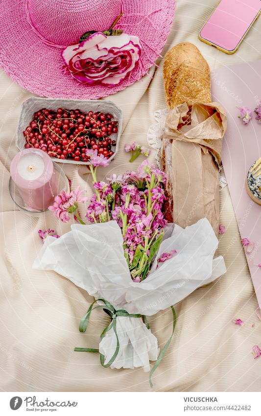 Pink hat with baguette , bunch of flowers and fruits on picnic blanket. Top view. Outdoor. pink top view outdoor outside tablecloth beautiful bread lunch