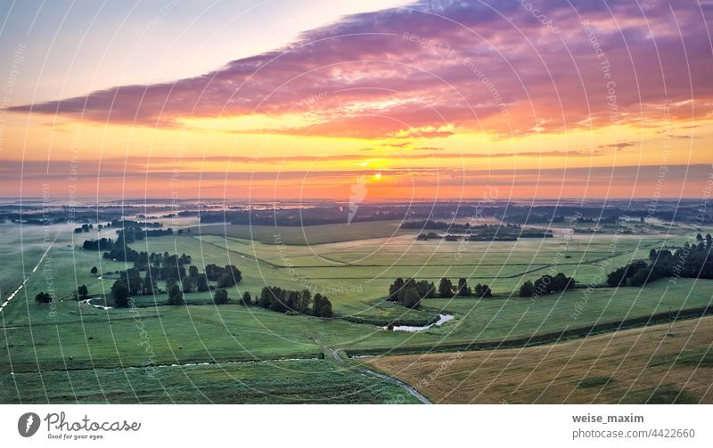 Dramatic summer sunrise. Panorama misty landscape. Foggy Morning on river aerial view. Green fields and meadows nature sky sunlight sunset outdoor clouds