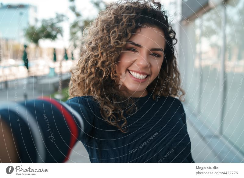 Young woman taking selfies outdoors. young urban city portrait street lifestyle casual female smiling posing one travel confidence take photo outside confident
