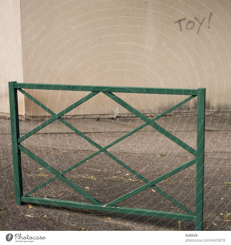 Toy with exclamation mark written on a wall toy Text writing Wall (building) Sidewalk rail Graffiti Asphalt Green Gray Beige Copy Space nobody Deserted