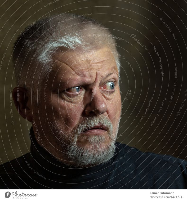 An older man with a beard looks to the side tensely. portrait Human being Face Man Dark Looking facial expression Facial expression Rembrandt Light Facial hair
