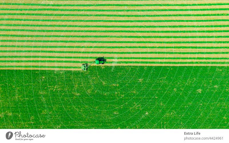 Aerial view of tractor as tow lawn mower machinery behind Above Agriculture Alfalfa Attached Clipper Clover Crop Cut Cutter Drag Farming Farmland Fast Field