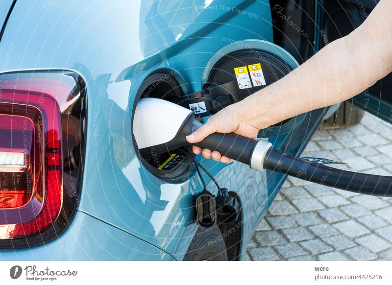 A woman's hand inserts a CCS charging plug into the connector of a blue electric vehicle CO²-neutrality electromobility Car Caucasian Charging plug Clean