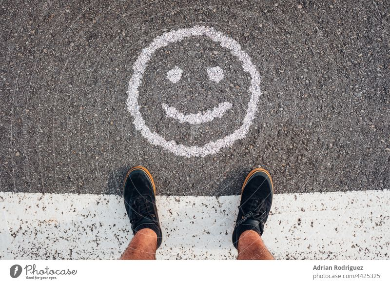 Person stands in front of a smile emoticon.  Concept for World Smile Day smiles Smiley face smile,expression Smile picture smile,expression,people smiled