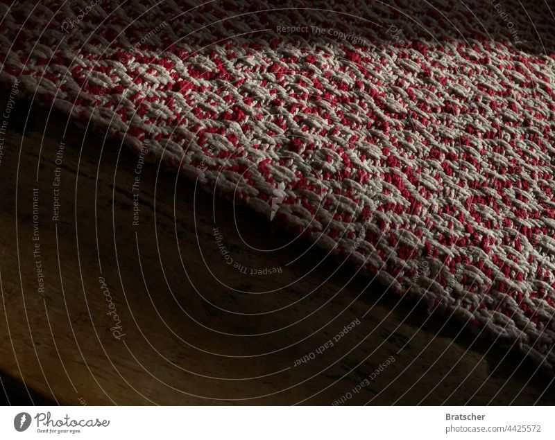 A traditionally handmade red and white tablecloth lies folded diagonally on an old, worn wooden table. Cloth Craft (trade) Table Woven weave Red White