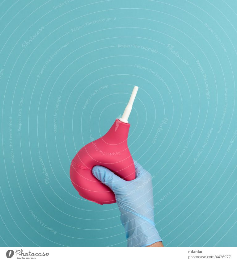 a hand in a blue medical glove holds a pink rubber enema on a blue background medicine hospital health care equipment doctor treatment pump disease injection
