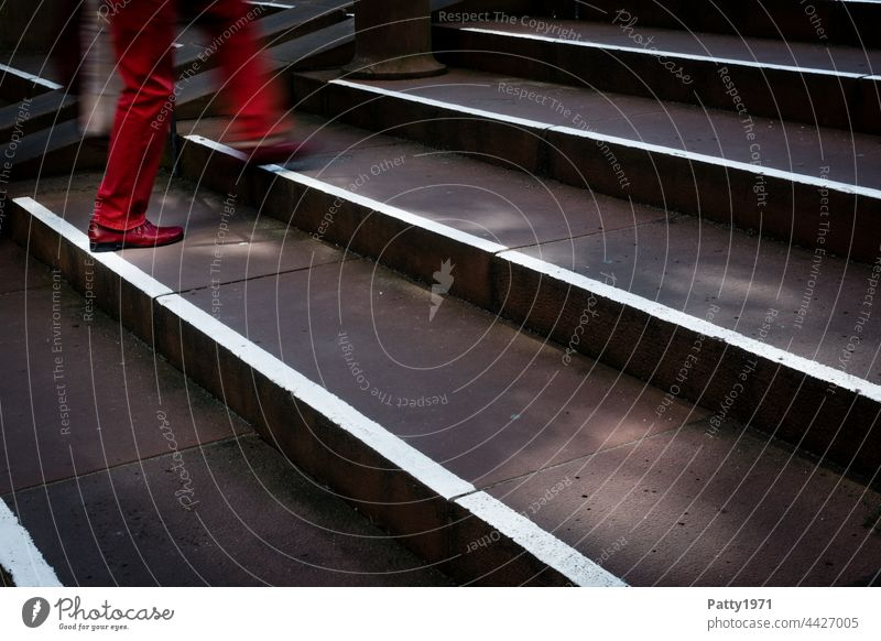 pedestrian in red trousers and shoes climbs a staircase - close up of legs Pedestrian Town Human being Stairs motion blur Going Shadow Light Exterior shot