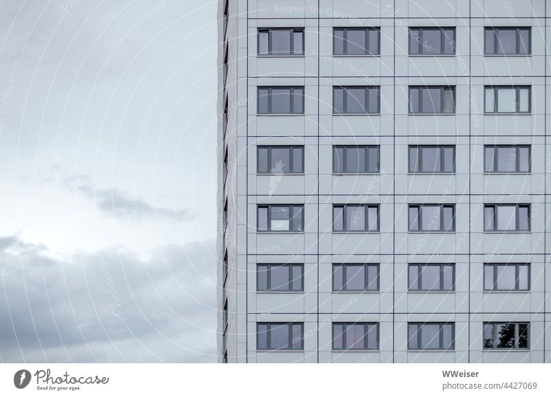 An apartment building with anonymous windows in front of a slightly cloudy evening sky Apartment Building Residential accommodation Student accommodation