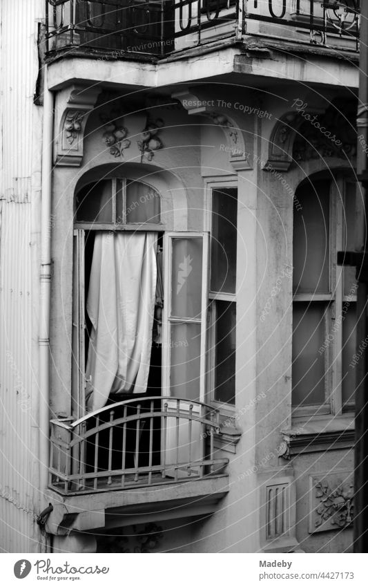 Open window with improvised curtain and small balcony of an old house in the alleys of Taksim in Istanbul on the Bosporus in Turkey, photographed in classic black and white