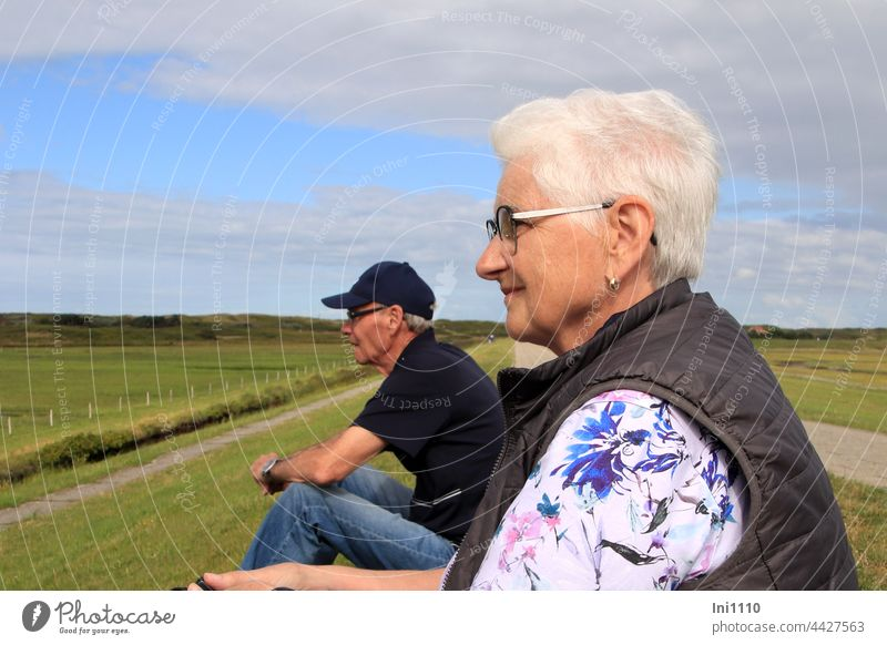 Senior couple sitting on the dike watching the birds vacation Relaxation North Sea blue sky with clouds Wangerooge Island Nature senior citizens Couple