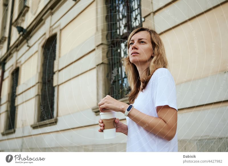 Woman walks at city street with paper coffee cup. woman drink casual relax freedom business girl urban model road person tea holding lifestyle takeaway