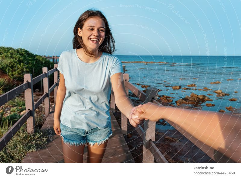 Happy teenage girls running on sidewalk by the sea at sunset young woman teenager hand mockup happy smiling t-shirt adolescent blue Caucasian walkside outdoor