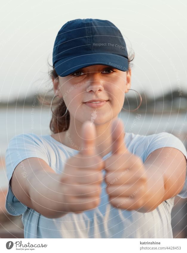 Teenage girl in blue baseball cap showing big thumbs up sunset teenager nature adolescent mockup smile head shot sea Caucasian outdoor vacation travel wearing