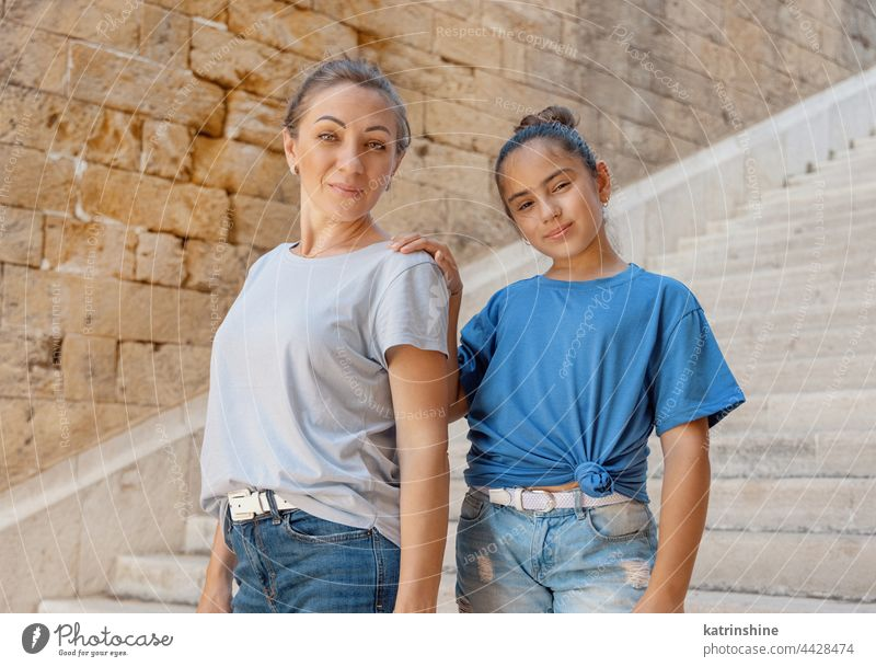 Mother and daughter standing on stone stairs outside Child kid girl mockup outdoor middle-aged woman schooler wearing t-shirts Stone embrace mom motherhood Blue