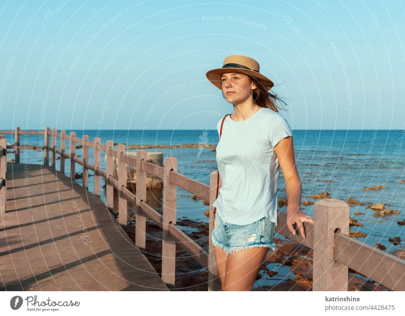 Teen girl standing on wooden bridge by the sea sunset teenager straw hat mockup Caucasian adolescent blue walkside sidewalk outdoor vacation travel look aside