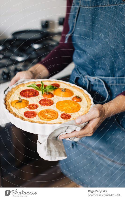 Female hands holding cheese and tomato quiche. tart red yellow ceramic dish pot seasonal basil baked circle food napkin