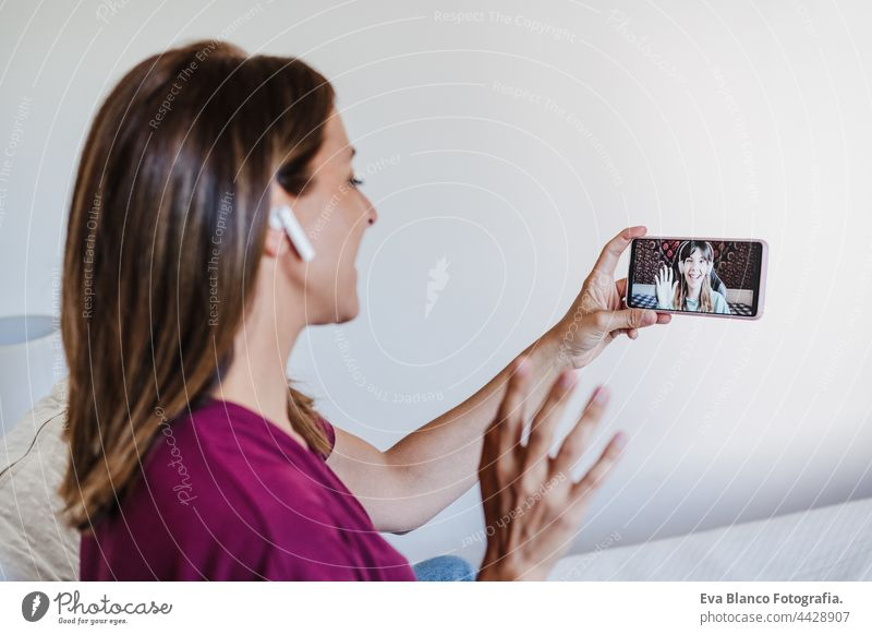 happy caucasian woman at home doing video call with friends on mobile phone. Home office and friendship bed 30s smiling beautiful young conversation digital