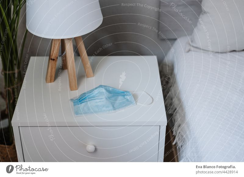 blue protective mask on bedside table on bedroom at home. Nobody. Corona virus and pandemic concept nobody corona virus face mask indoor interior design