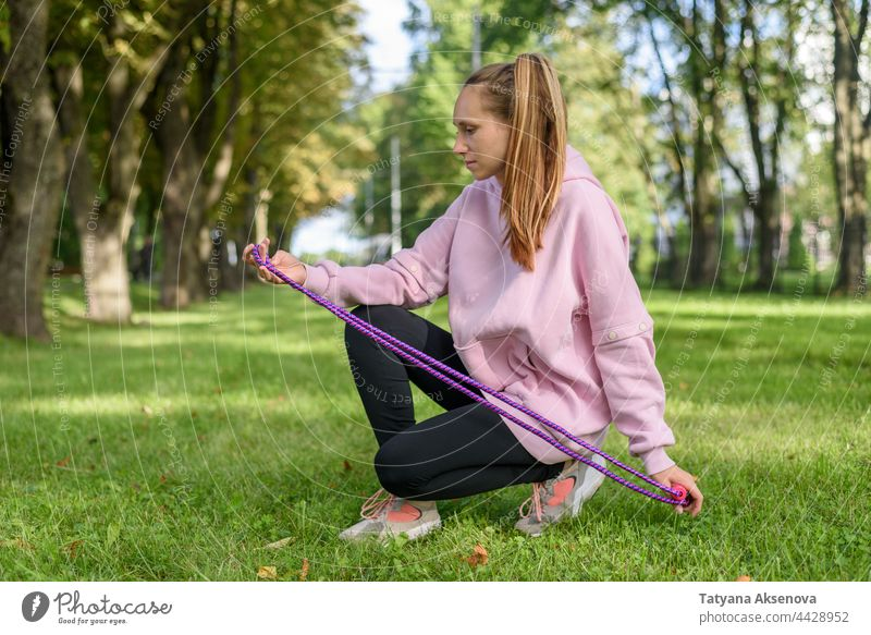 Young woman with skipping rope female young jumping jumping rope tall thin real activity cardio city street outdoor morning hoodie caucasian ethnicity