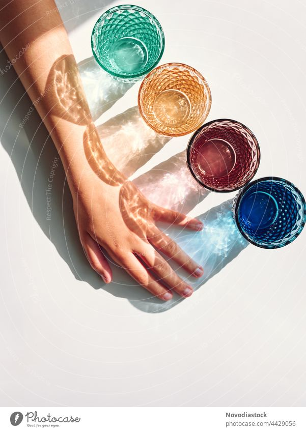 Colorful glasses with shadows and a girl's arm isolated on a white background Drinking Beverage Colour photo Interior shot Glass Drinking water Day Water Fluid