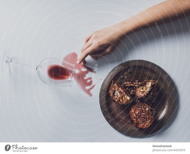 One arm, a plate with pomegranates and a wine of glass spilled on a table Hand Fingers Woman Human being Plate Colour photo Interior shot Arm Pomegranate Shadow