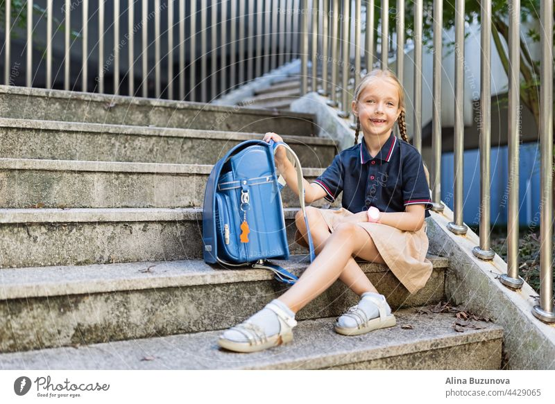 Schoolgirl back to school after summer vacations. Child in uniform with backpack early morning outdoor. education public school schoolchild student pupil