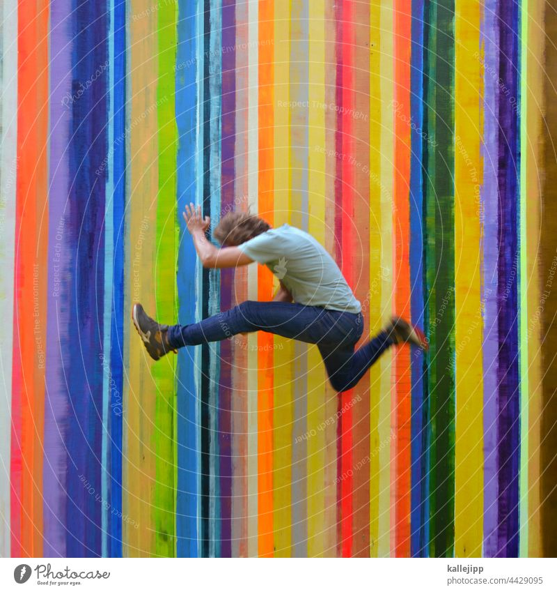 Colourful color strip Colour photo Jump Man Human being Hop colourful variegated Rainbow Stripe Athletic Sports Joy Exterior shot Youth (Young adults) Playing