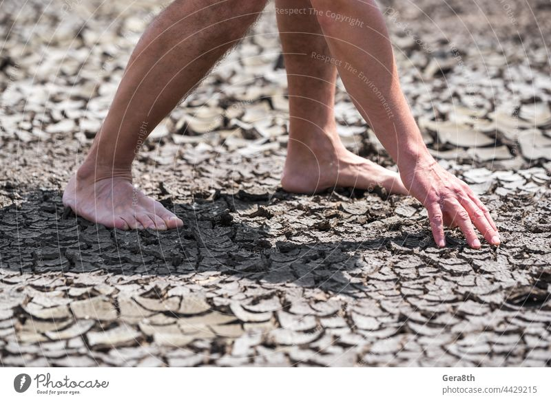 bare feet of a person on dry soil without plants close up arid background bad ecology barefoot climate cracks crisis desert disaster drought earth environment