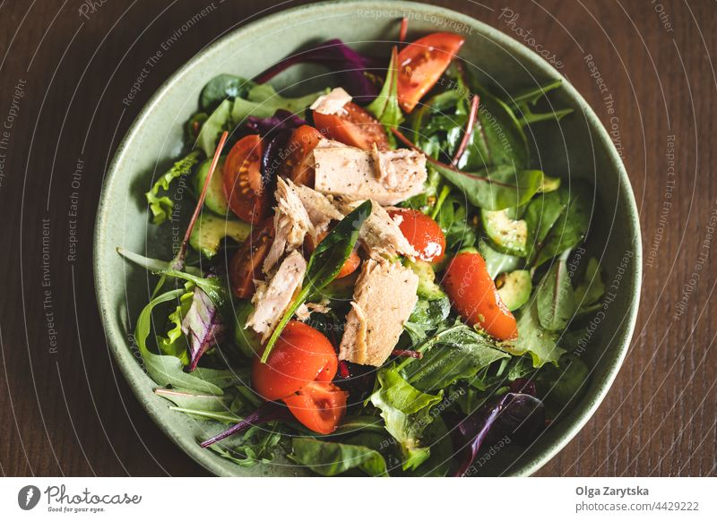 Tuna salad in bowl with black fork. tuna green tomato cucumber avocado close up arugula red chard vegan vegetarian food healthy top view directly above