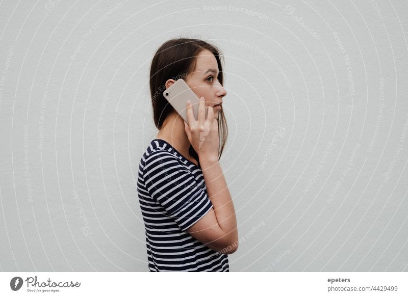 Young woman holding a smartphone to the ear and standing in front of a white wall brown hair casual clothes copy space gen z getting news millenial