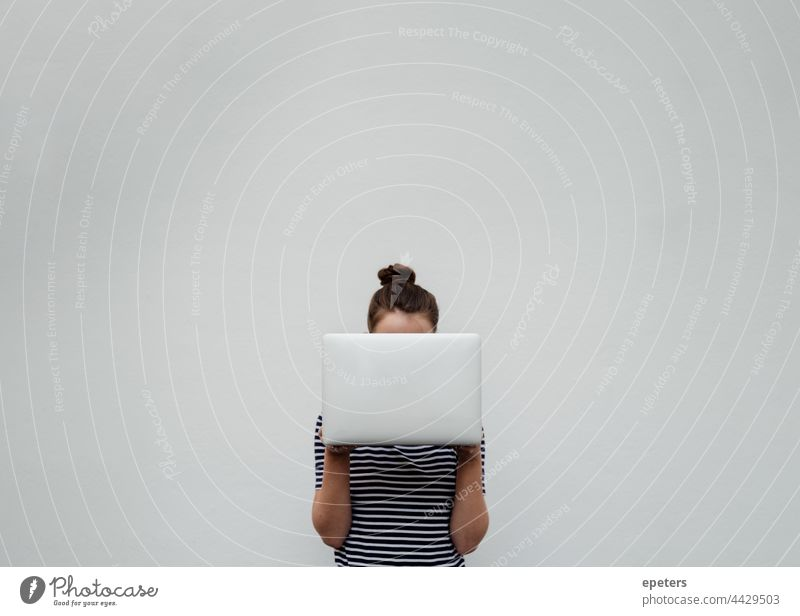 Young woman in jeans and t-shirt holds a silver laptop in front of her face brown hair Computer Self-confident Copy Space hide behind a computer Participation