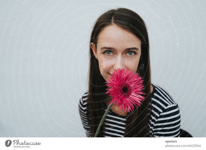 Smiling young woman hides behind a flower that partially covers her face Bright brown hair Easygoing Copy Space Face Flower kind Gerbera green eyes hiding