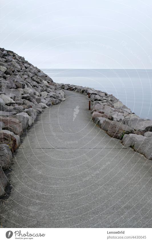 An empty path leading around a curve at the coast of Keflavík, Iceland background beach beautiful blue calm coastline iceland keflavik keflavík landscape nature