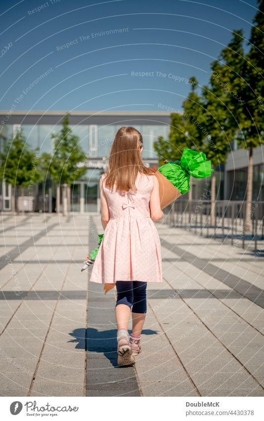 A girl goes to school with a school bag for enrollment Girl School candy cone sugar cone First day at school Child Colour photo Infancy Education Study