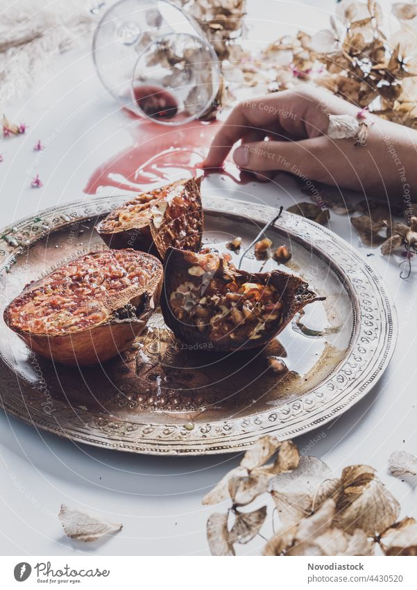 Pomegranates on a plate made of steel, one hand a glass on a table, still life Plate Crockery Colour photo Interior shot Food Hand Table Food photograph