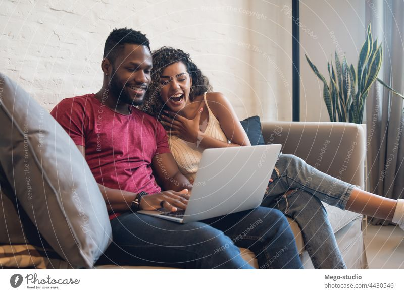 Couple using a laptop while sitting on a couch at home. couple man woman two lifestyle together sofa relationship boyfriend girlfriend modern male female