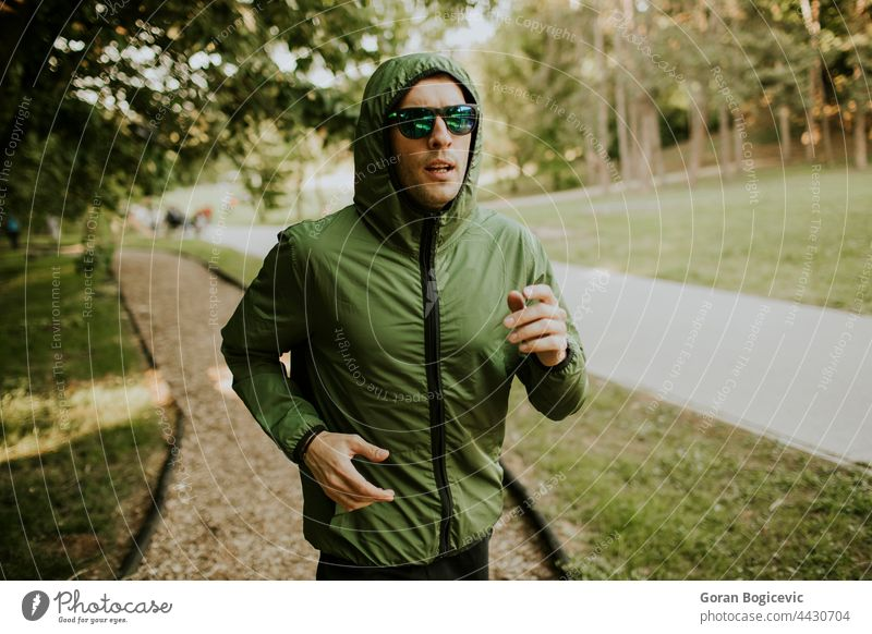 Athletic young man running while doing workout in sunny green park action active activity adult athlete athletic caucasian endurance exercise fit fitness grass