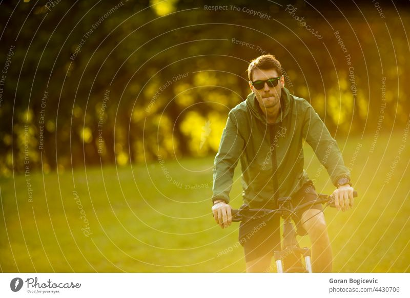 Young man riding ebike in the park active battery bicycle biker biking black cyclist e-bike eco ecologic ecology electric electro energy engine equipment