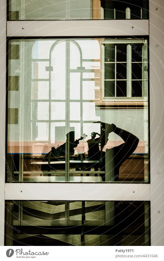 Human silhouettes in front of a geometric facade reflected in a glass pane | Order in chaos Silhouette Human being Window Glass reflection Reflection