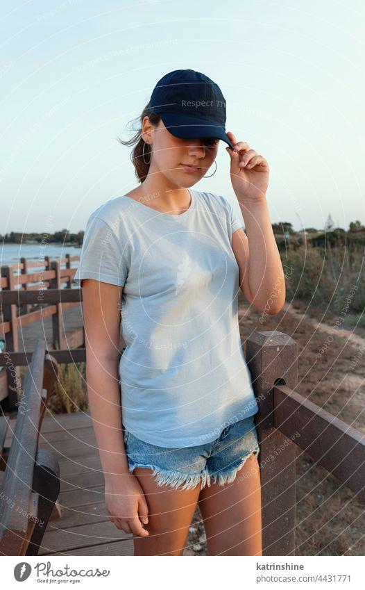 Teen girl in dark blue baseball cap and t-shirt outdoor teenager adolescent Caucasian mockup sea visor wearing t-shirts teen girl sidewalk bridge childhood