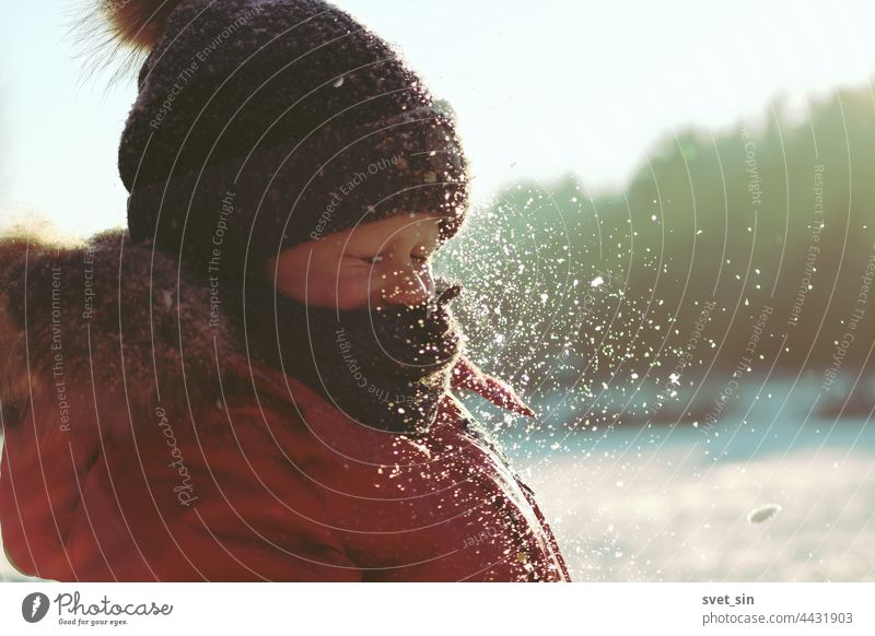 Snowflakes sparkle in the sunlight in the air in front of the face of a child who has closed his eyes. A boy in winter clothes plays with snow outdoors on a frosty sunny winter day.